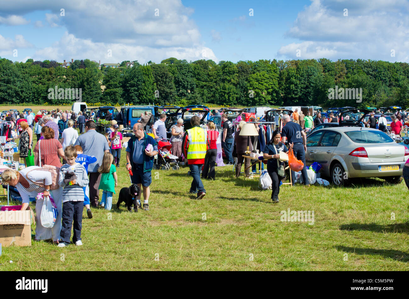 Sellers and buyers at a car boot sale stock image