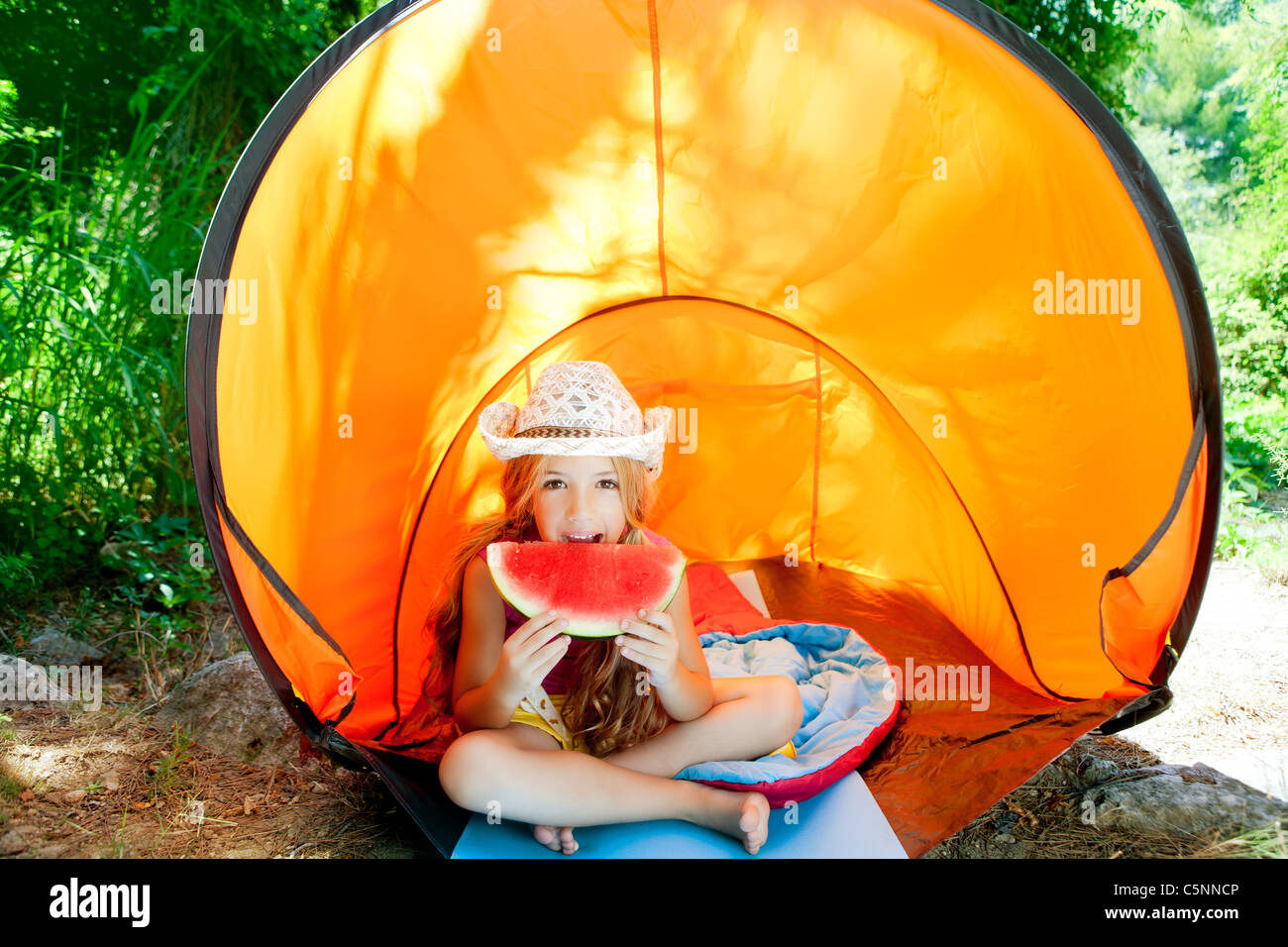 C&ing children girl in tent eating watermelon slice fruit in outdoor forest & Camping children girl in tent eating watermelon slice fruit in ...