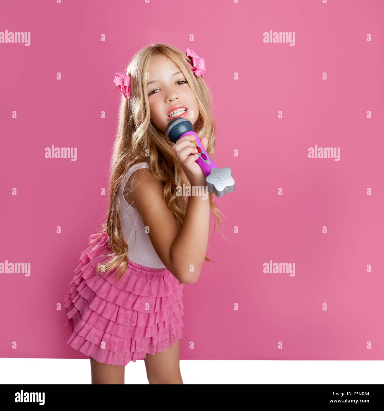 Children Little Star Singer Like Blond Fashion Doll With Mic Over Pink  Background - Stock Photo