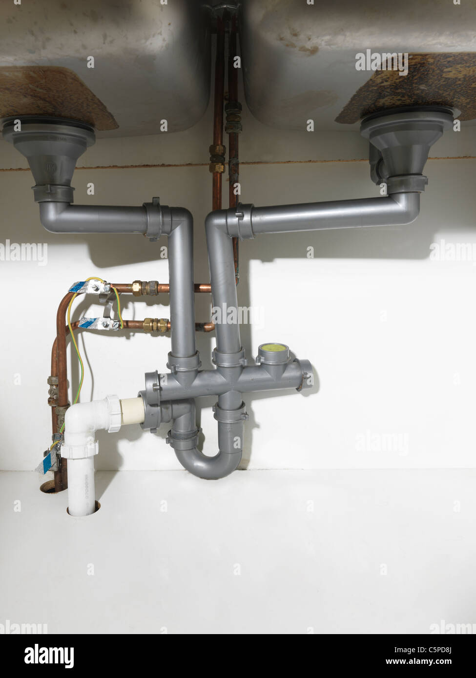 stock photo waste pipe and fittings under a double kitchen sink and earth bonding wires with copper pipes - Kitchen Sink Wastes