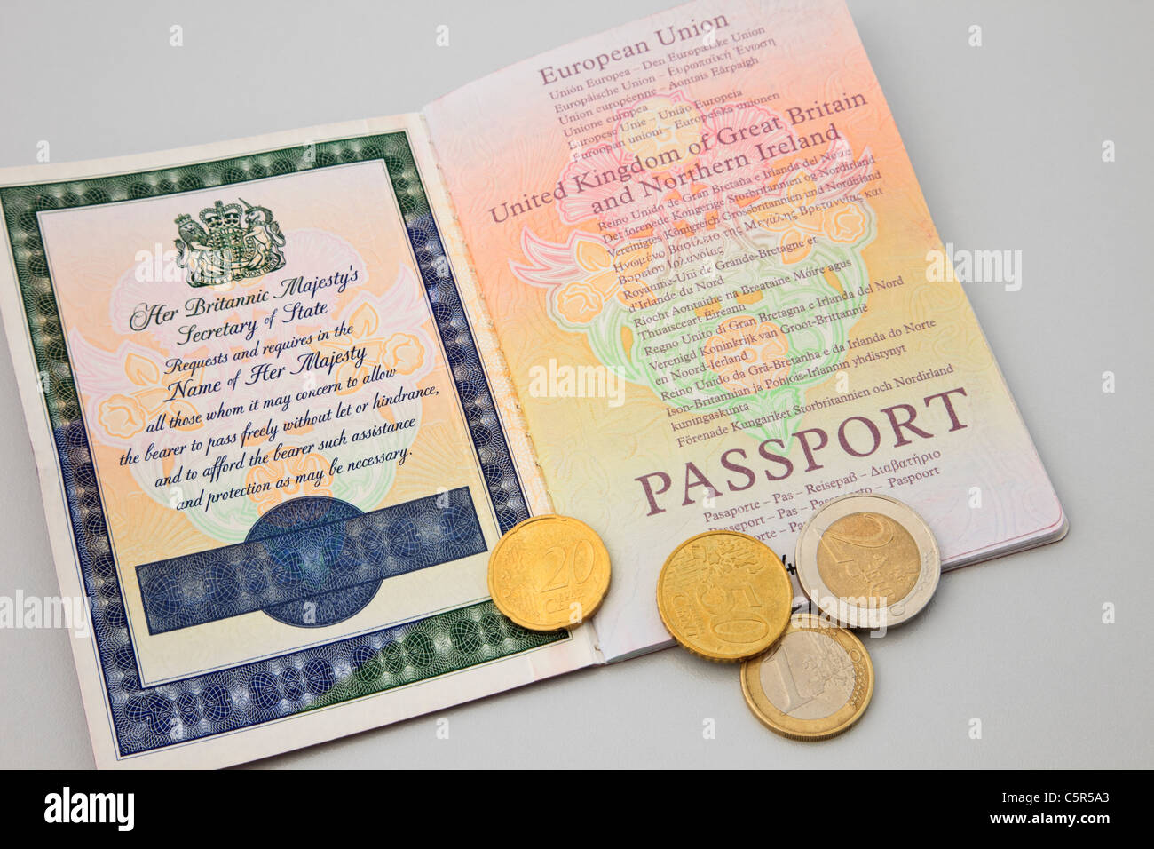 Uk, Britain A British Passport Open With Some Euro Coins For Travelling In  The British