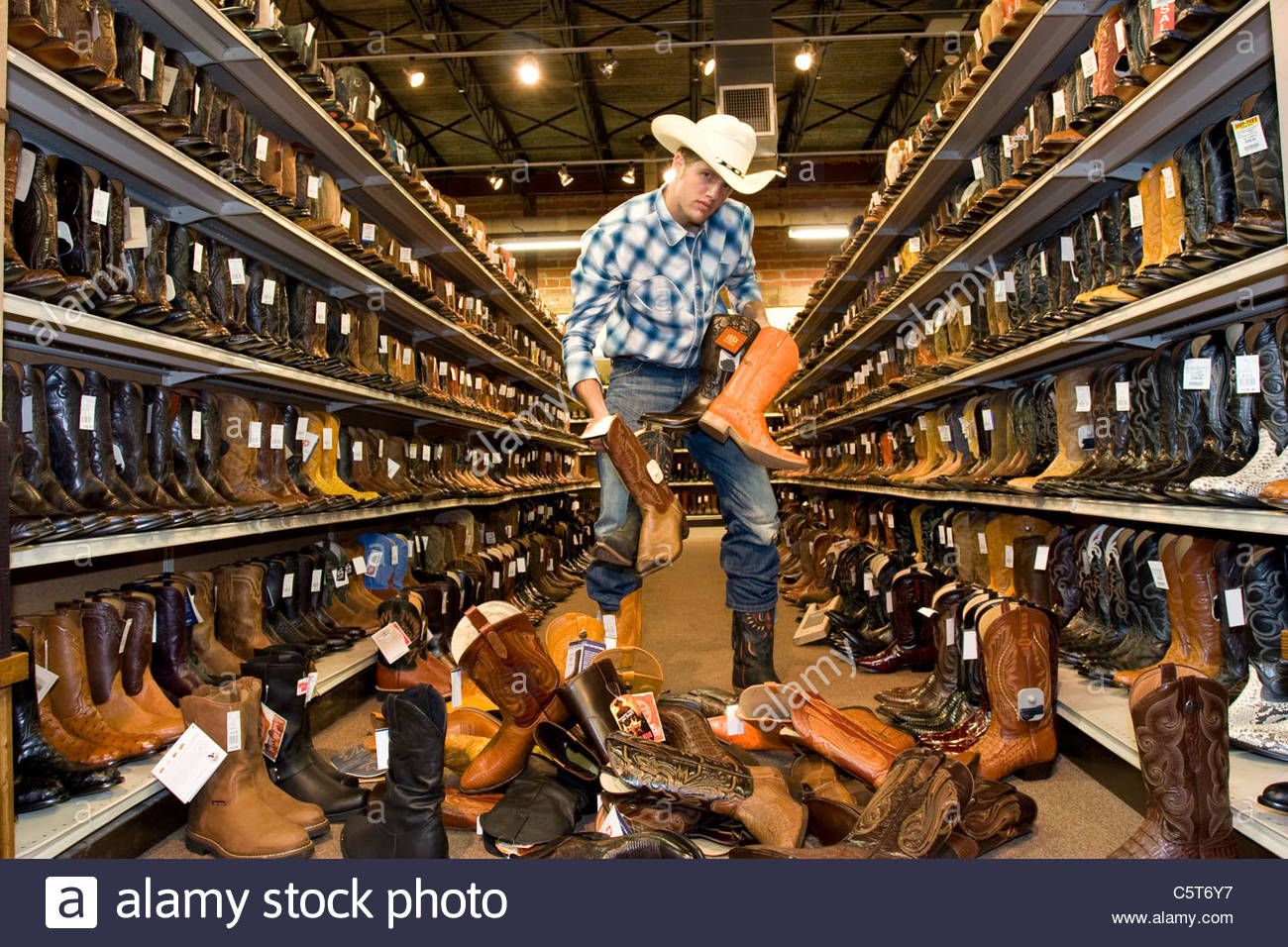 USA, Texas, Dallas, Young man choosing cowboy boots in shoe store ...