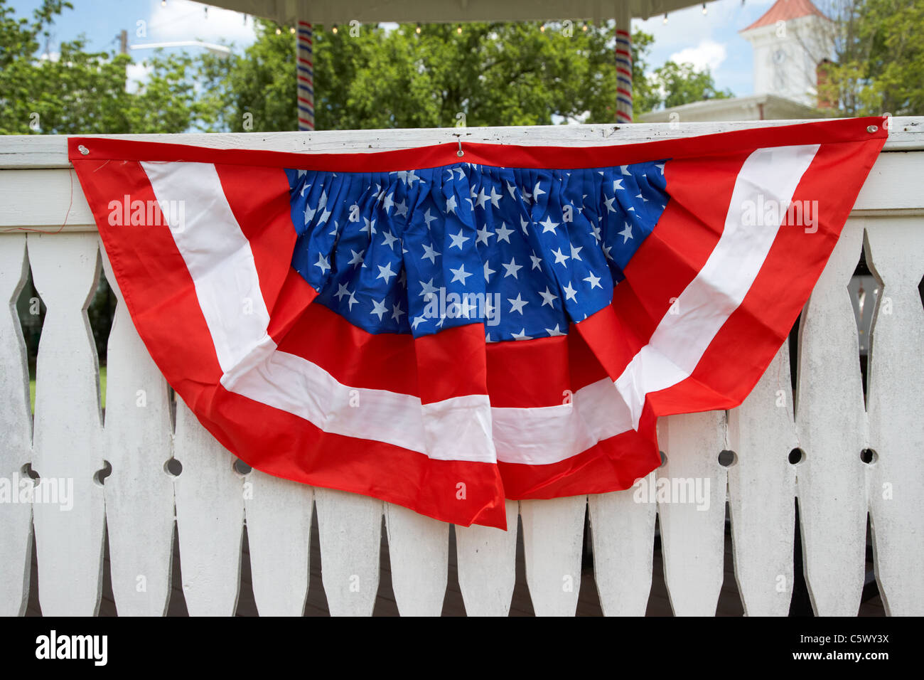 red white and blue american flag bunting put out on white fence ...