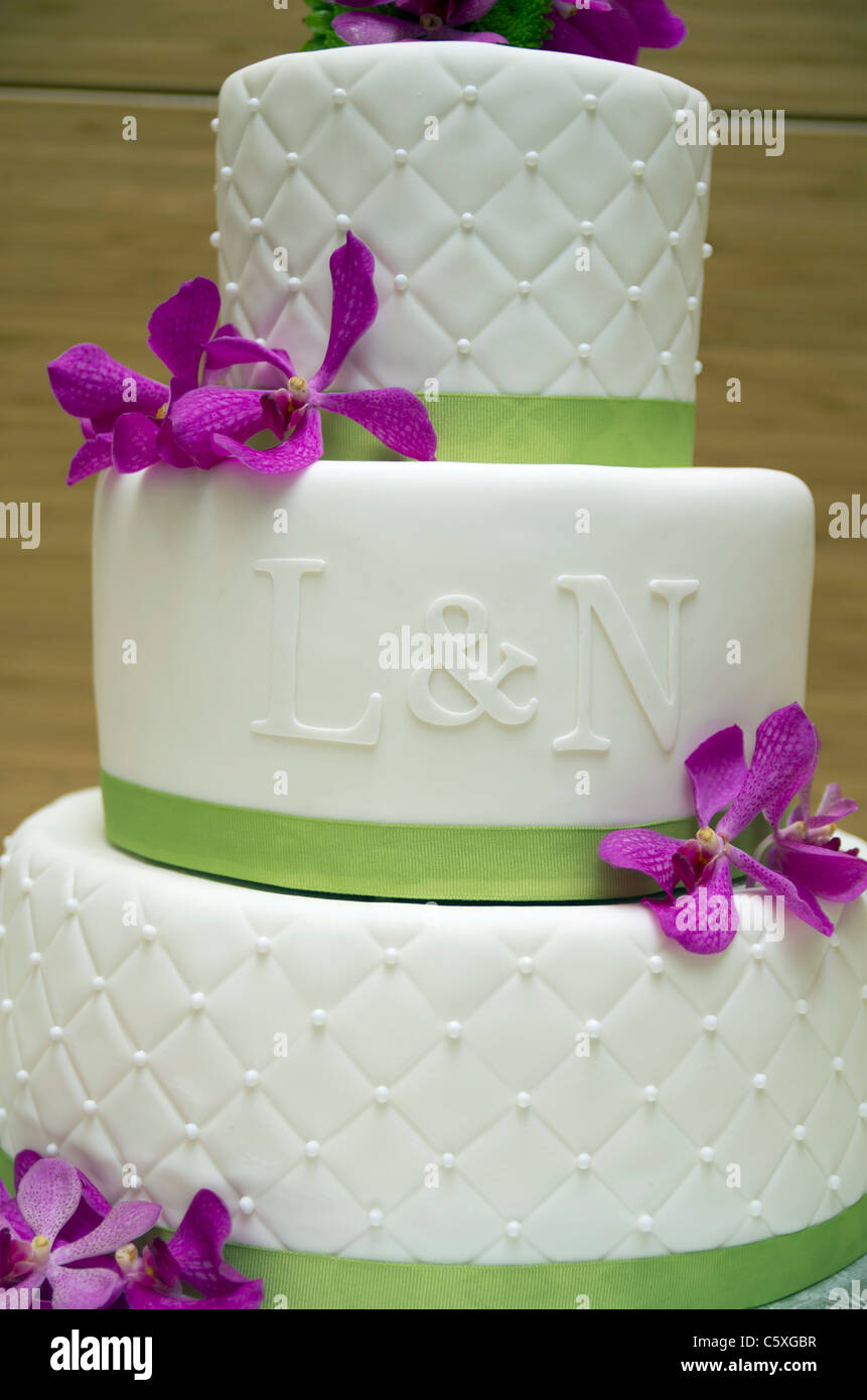 A wedding cake with purple flowers, white ganache and green ribbon ...