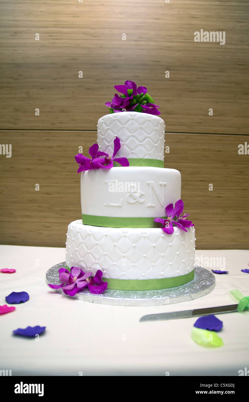 A Wedding Cake With Purple Flowers White Ganache And Green Ribbon The Letters L N On Front