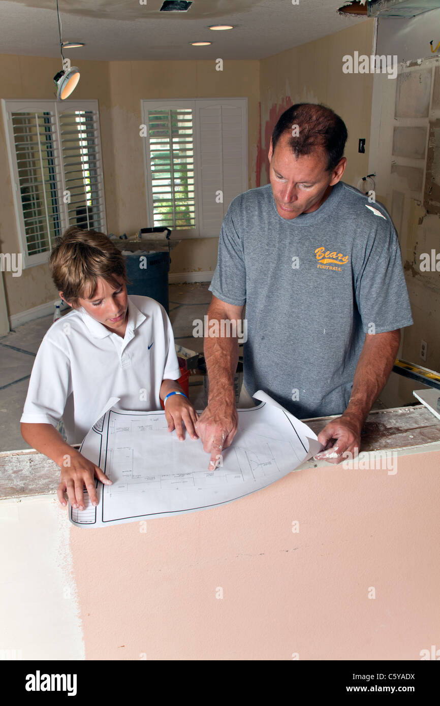 Caucasian father and 11 12 year years old son boy helping work stock caucasian father and 11 12 year years old son boy helping work experience together read blueprint pattern plans remodel kitchen mr myrleen pearson malvernweather Image collections