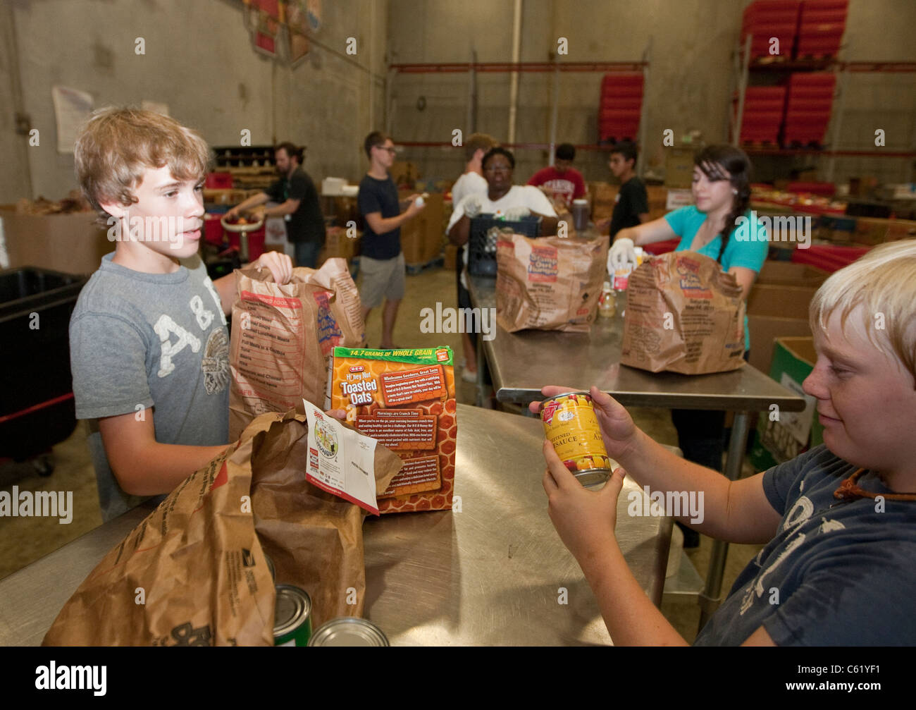 Teens volunteer sorting cans of food in the warehouse of the San