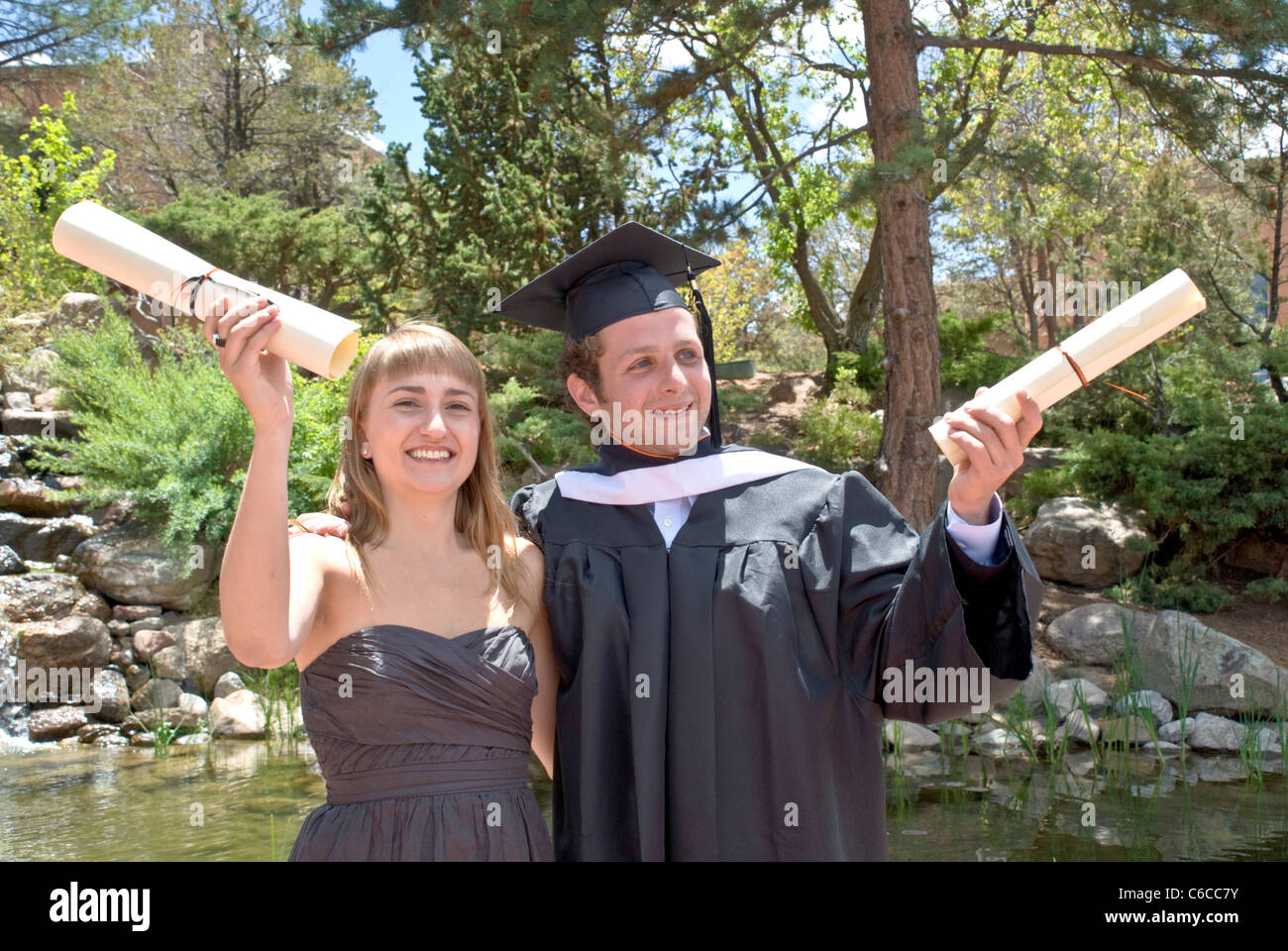 two graduates wave their diplomas after graduating from st johns stock photo two graduates wave their diplomas after graduating from st johns college in santa fe new