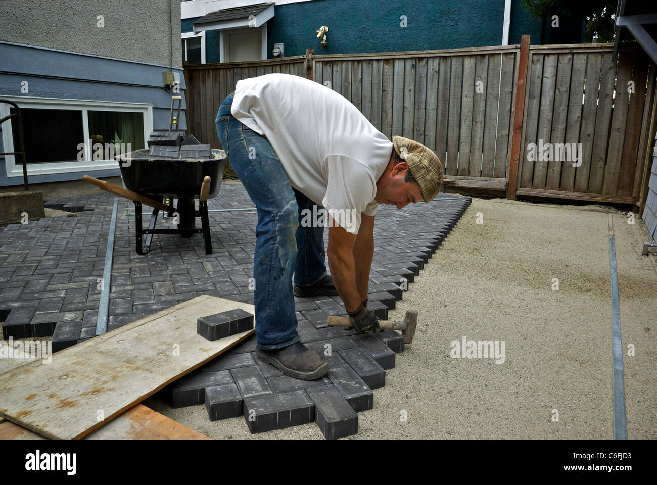 Stock Photo   Stonemason Laying Patio Construction Bricks Sand Gravel Base  Backyard
