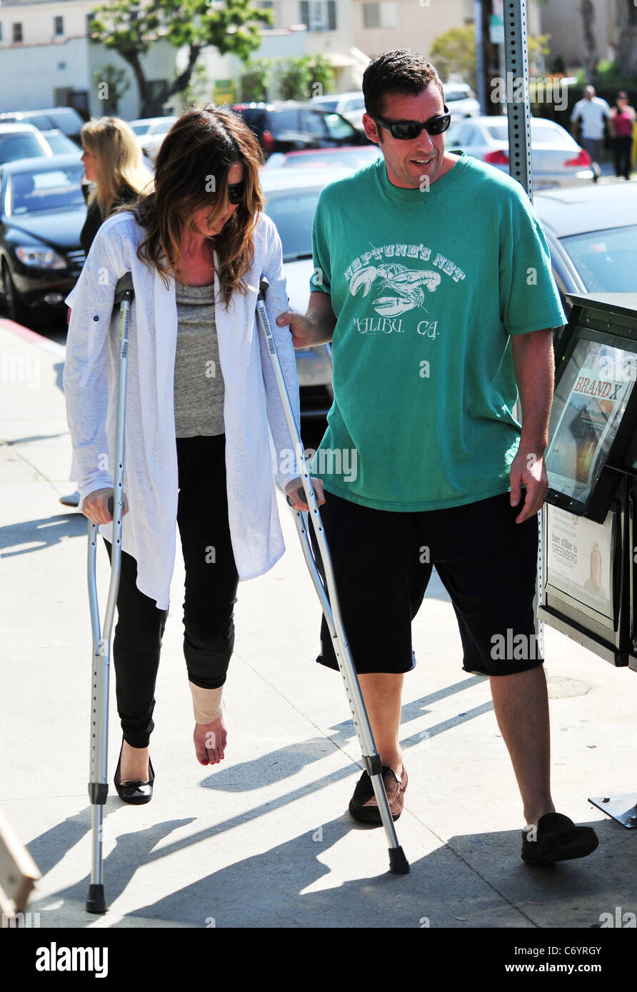 Adam sandler helps his wife jackie as she walks on her crutches stock