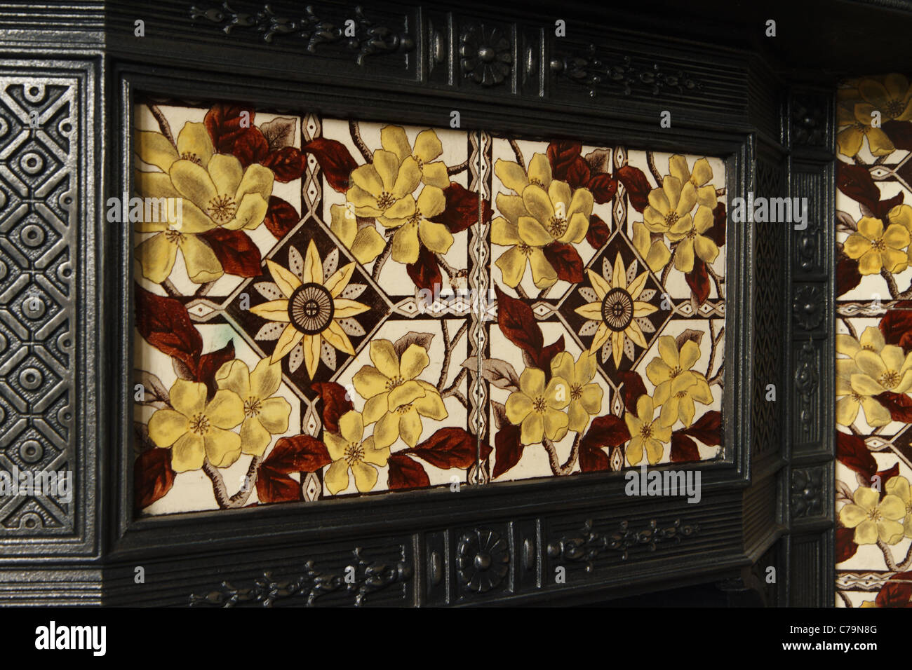 victorian cast iron fireplace with inlaid ceramic tiles stock
