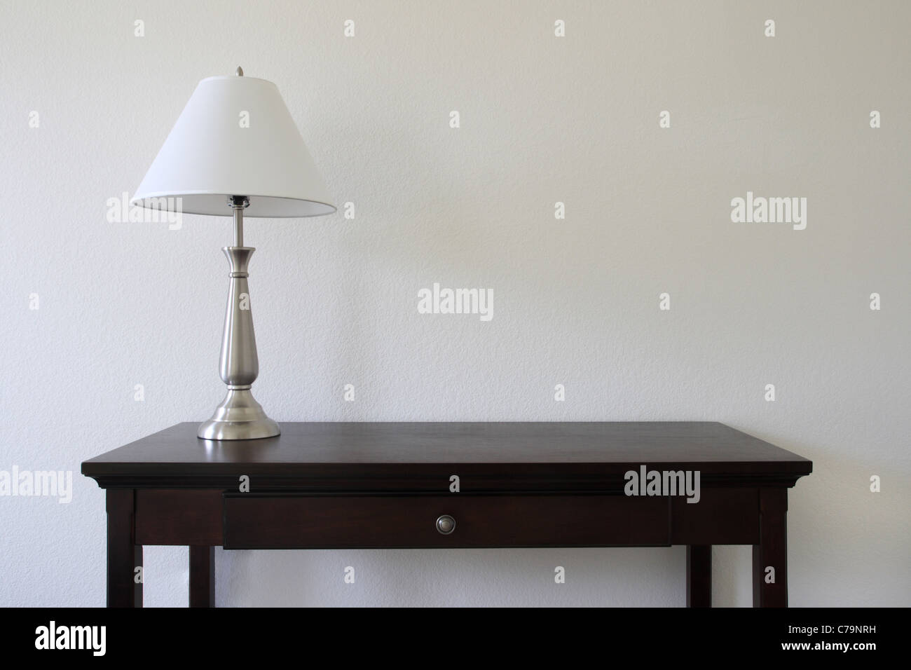 Silver table lamp sitting on a wooden table with a white wall in stock photo silver table lamp sitting on a wooden table with a white wall in the background and copy space geotapseo Images