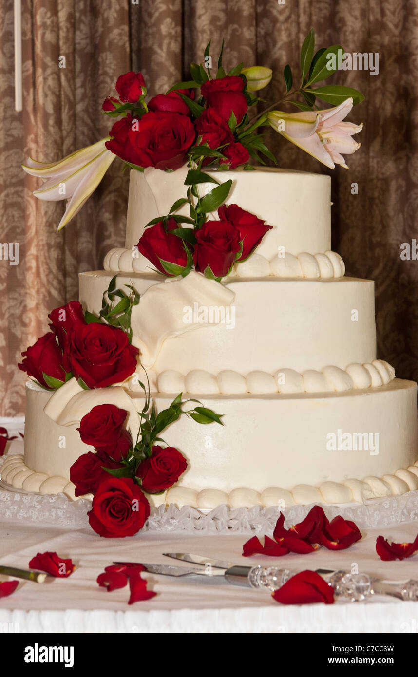 Large Multi Tier Wedding Cake Decorated With Red Rosesknife And Server On Table Covered White Cloth Roses Petals