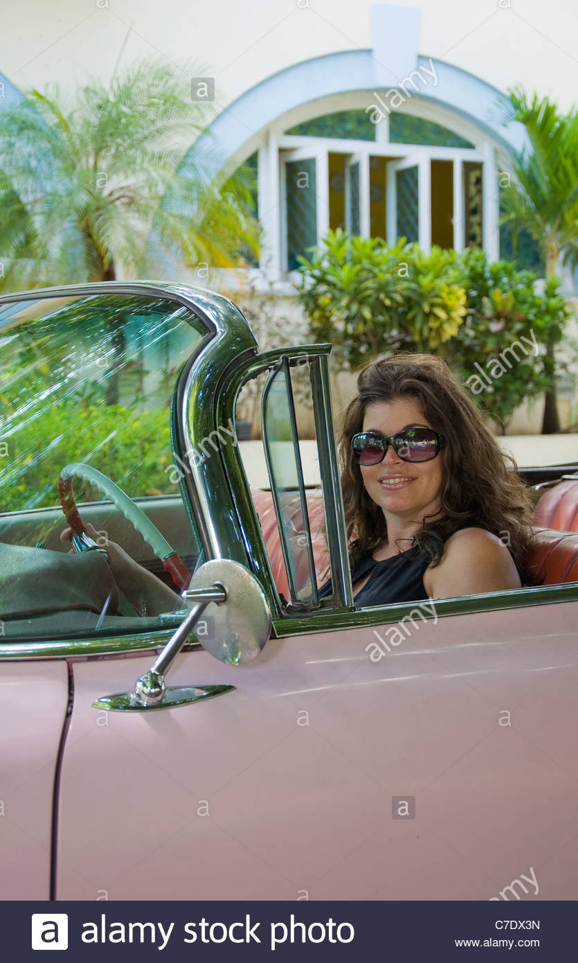 Hispanic Woman Driving A Car From The 1950s Retro Car And Latin