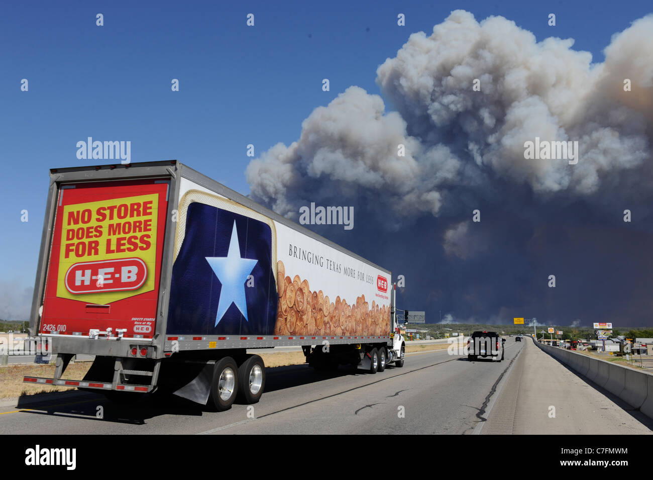 Grocery delivery truck with the texas lone star visible drives toward smoke from a wildfire burning