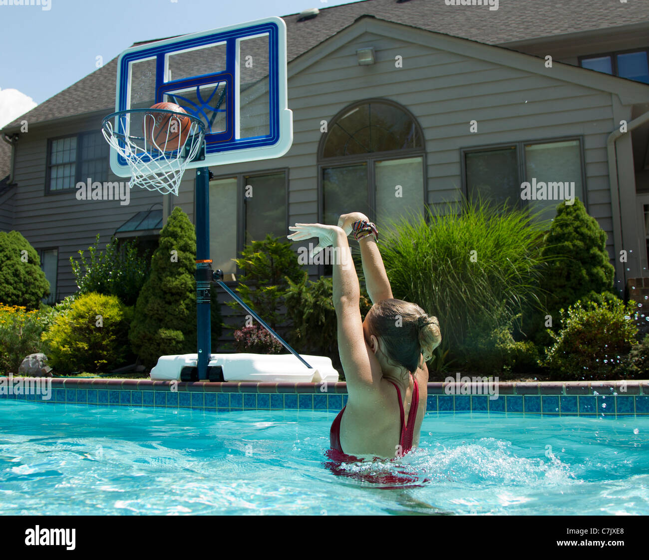 young shooting a basketball in a backyard swimming pool stock