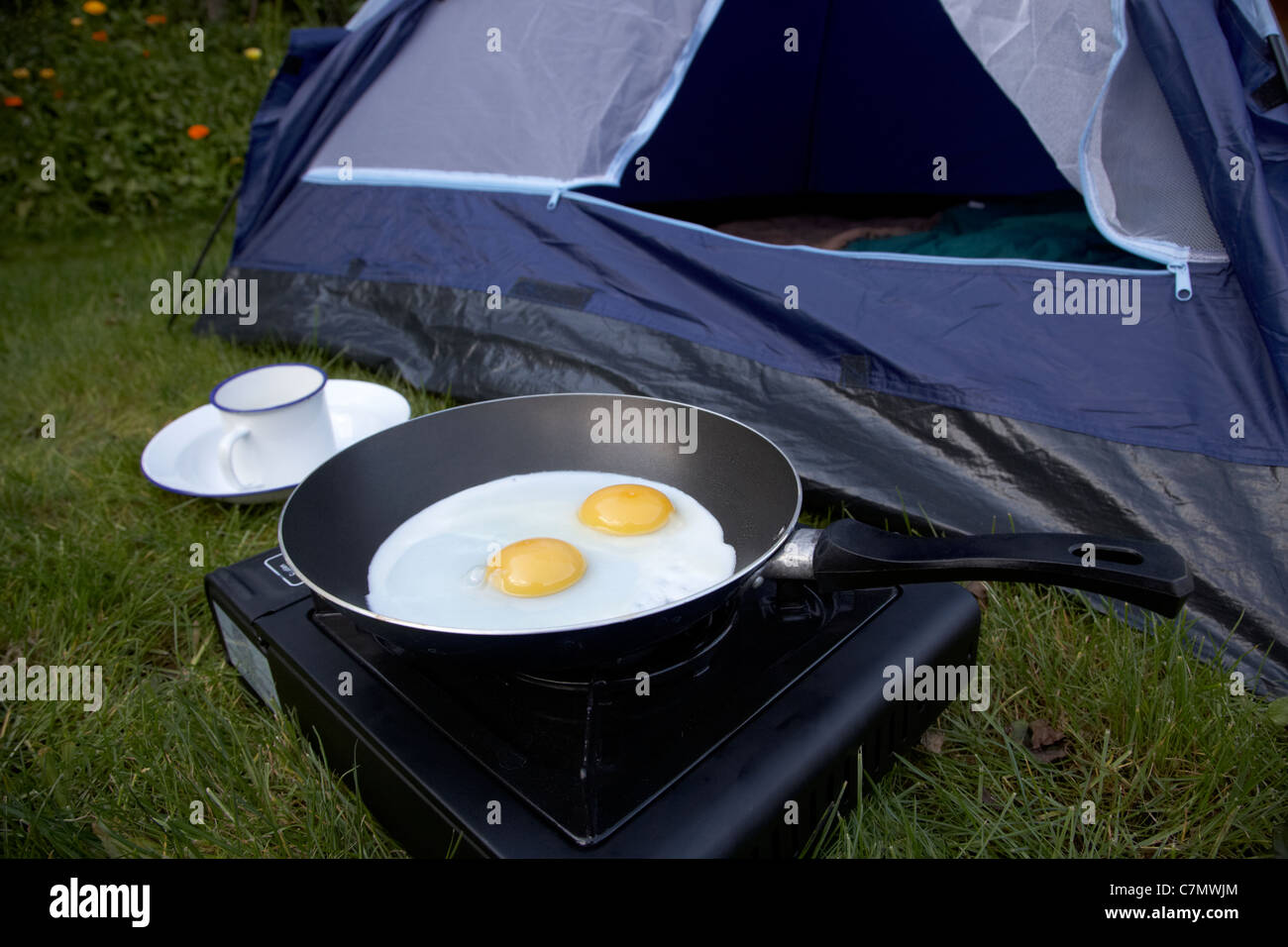 cooking two fried eggs on a small portable gas c&ing stove in front of the open door of a dome tent & cooking two fried eggs on a small portable gas camping stove in ...