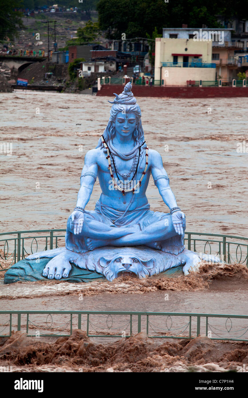 A blue statue of Lord Shiva submerging in the flood waters ...
