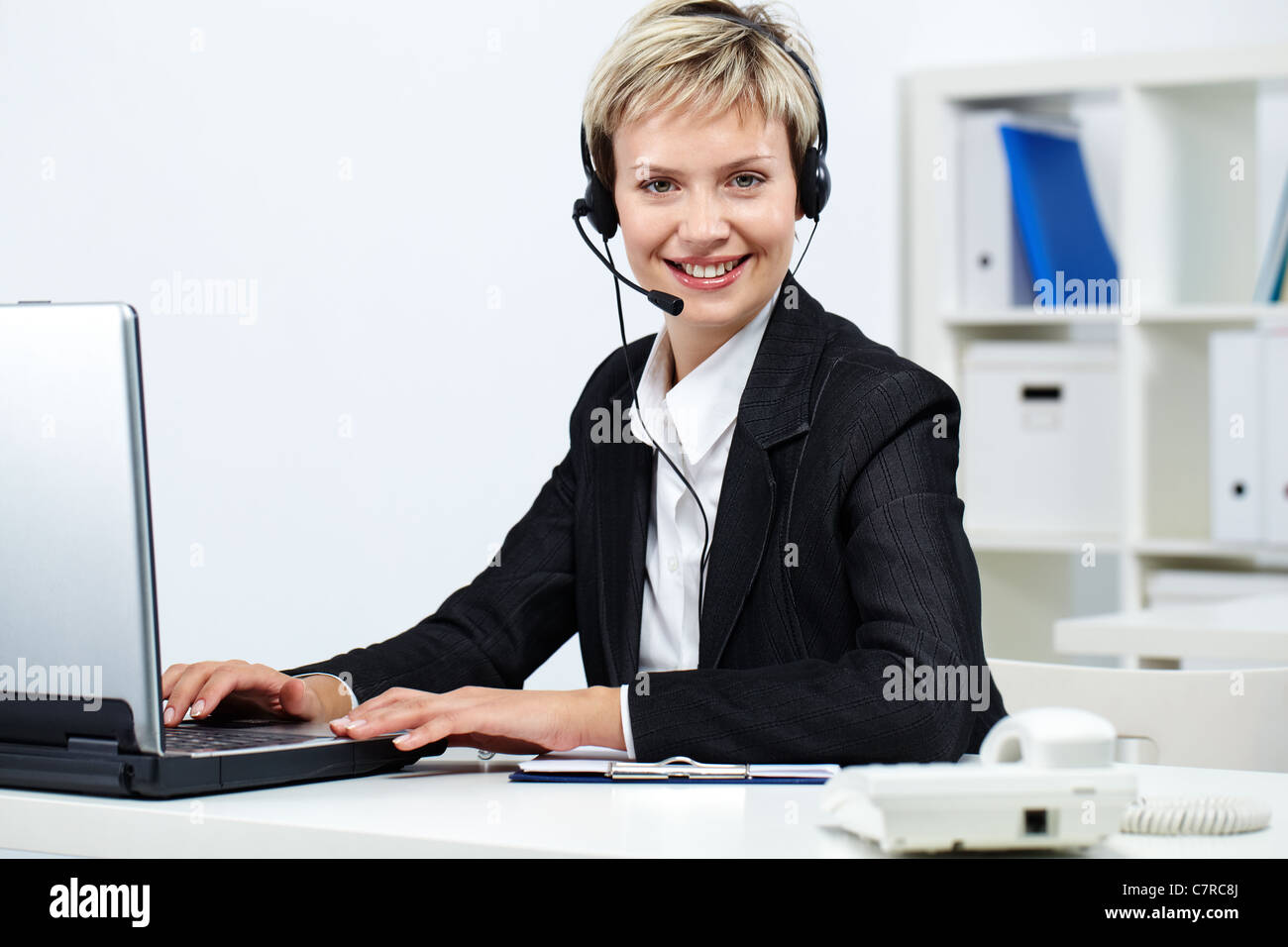 Young pretty receptionist with headset at computer looking at young pretty receptionist with headset at computer looking at camera and smiling sciox Images