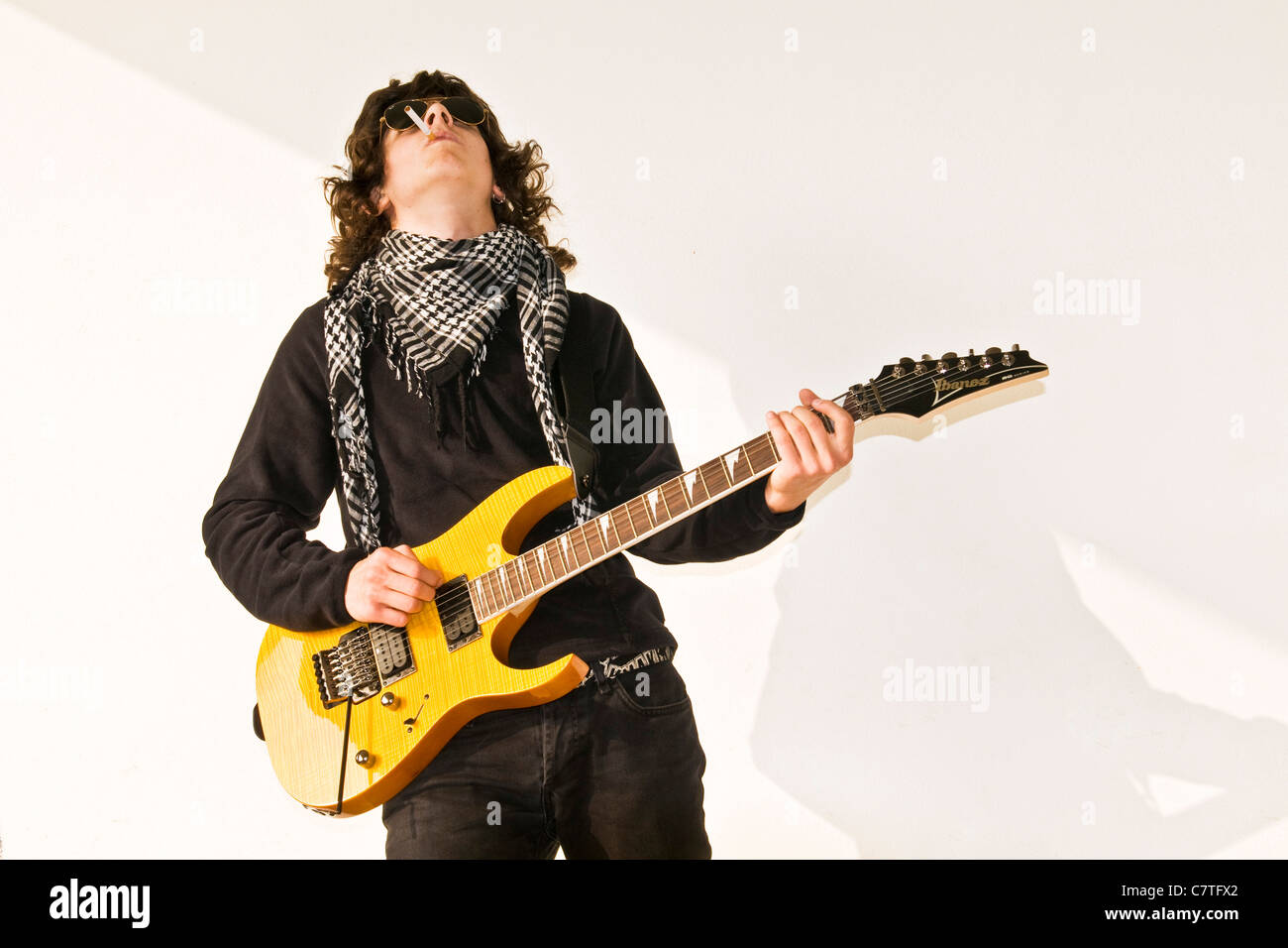Fingerless gloves for guitarists - Teenage Boy Playing Bass Guitar Stock Image
