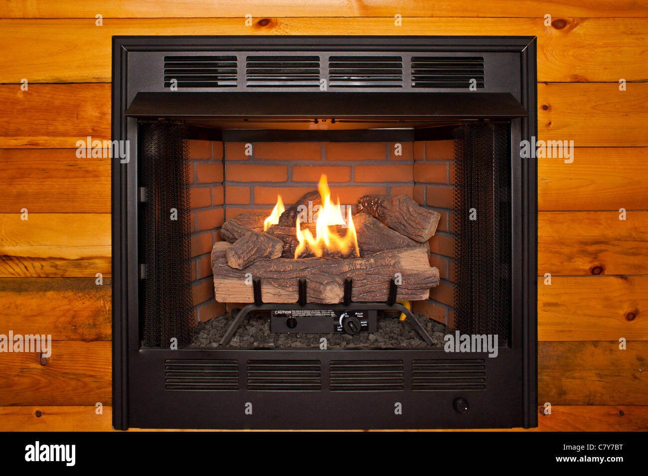 Lit electric fireplace built into log cabin wall Stock Photo ...