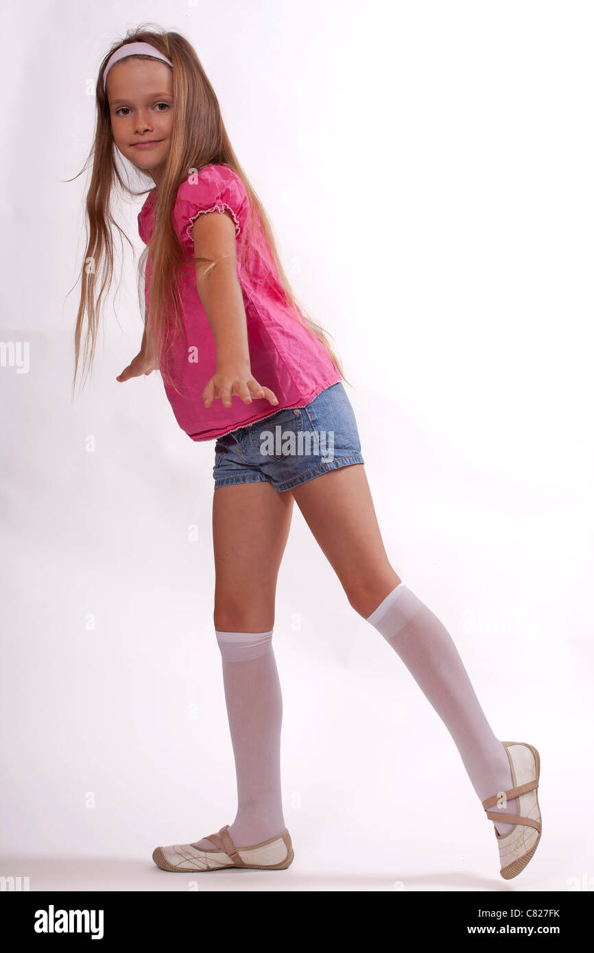 preteen in stockings 8 year old girl dancing in shorts and shirt - Stock Image