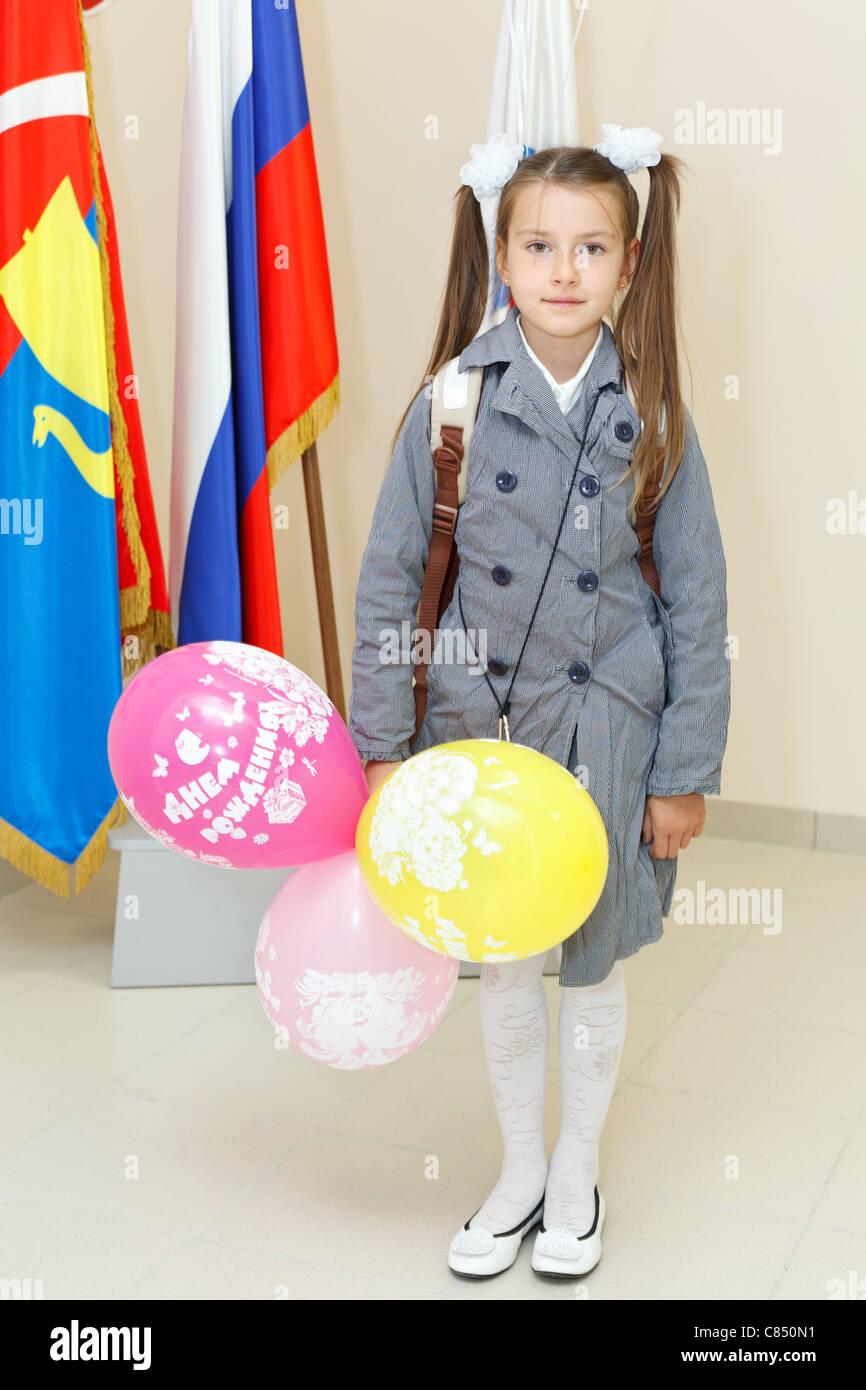 russian schoolgirl Russian schoolgirl standing near schools flags at September first in Russia.  - Stock Image