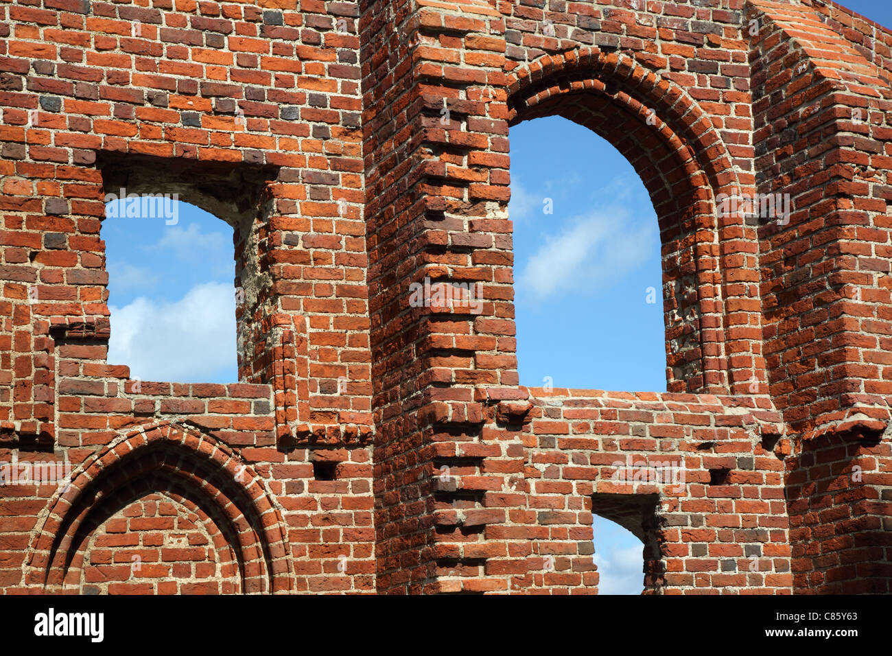 Blue Sky In Holes On Old Red Brick Wall