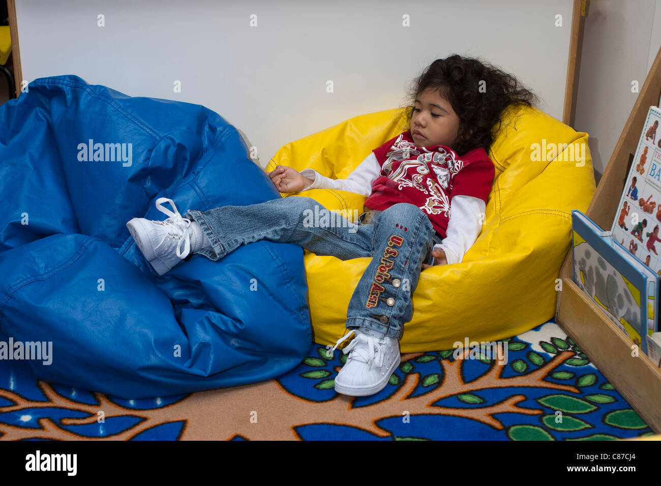 Preschool Classroom 4 Year Old Girl Relaxing On A Beanbag Chair During School