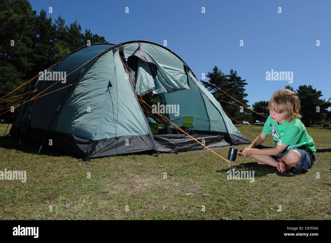 a young boy bangs in pegs on tent during c&ing vacation holiday & a young boy bangs in pegs on tent during camping vacation holiday ...