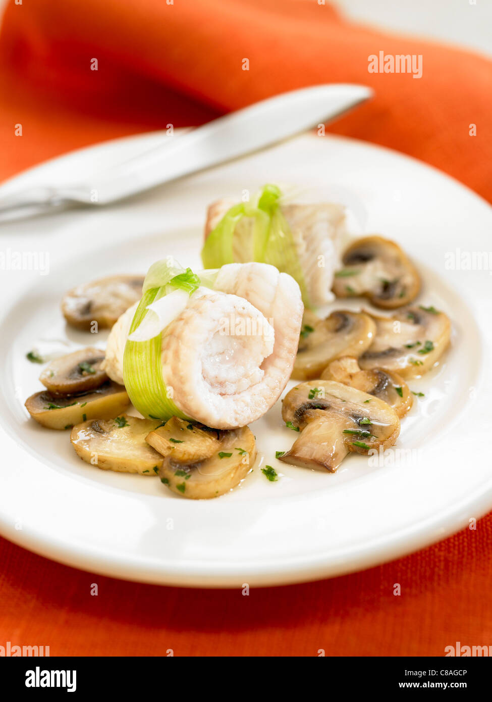 rolled sole fillets with button mushrooms stock photo