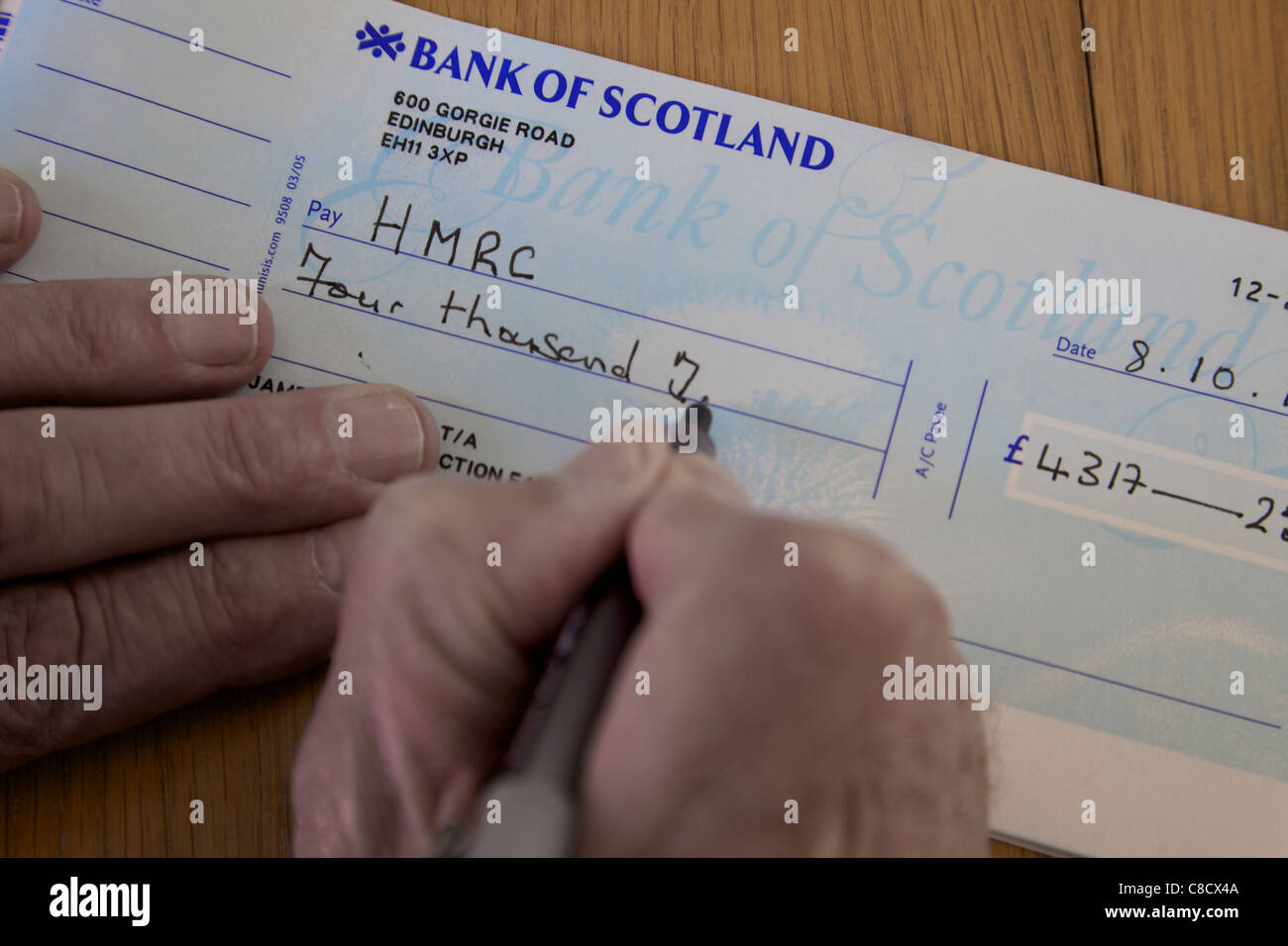 Old cheque stock photos old cheque stock images alamy writing a cheque for hmrc tax england stock image ccuart Images