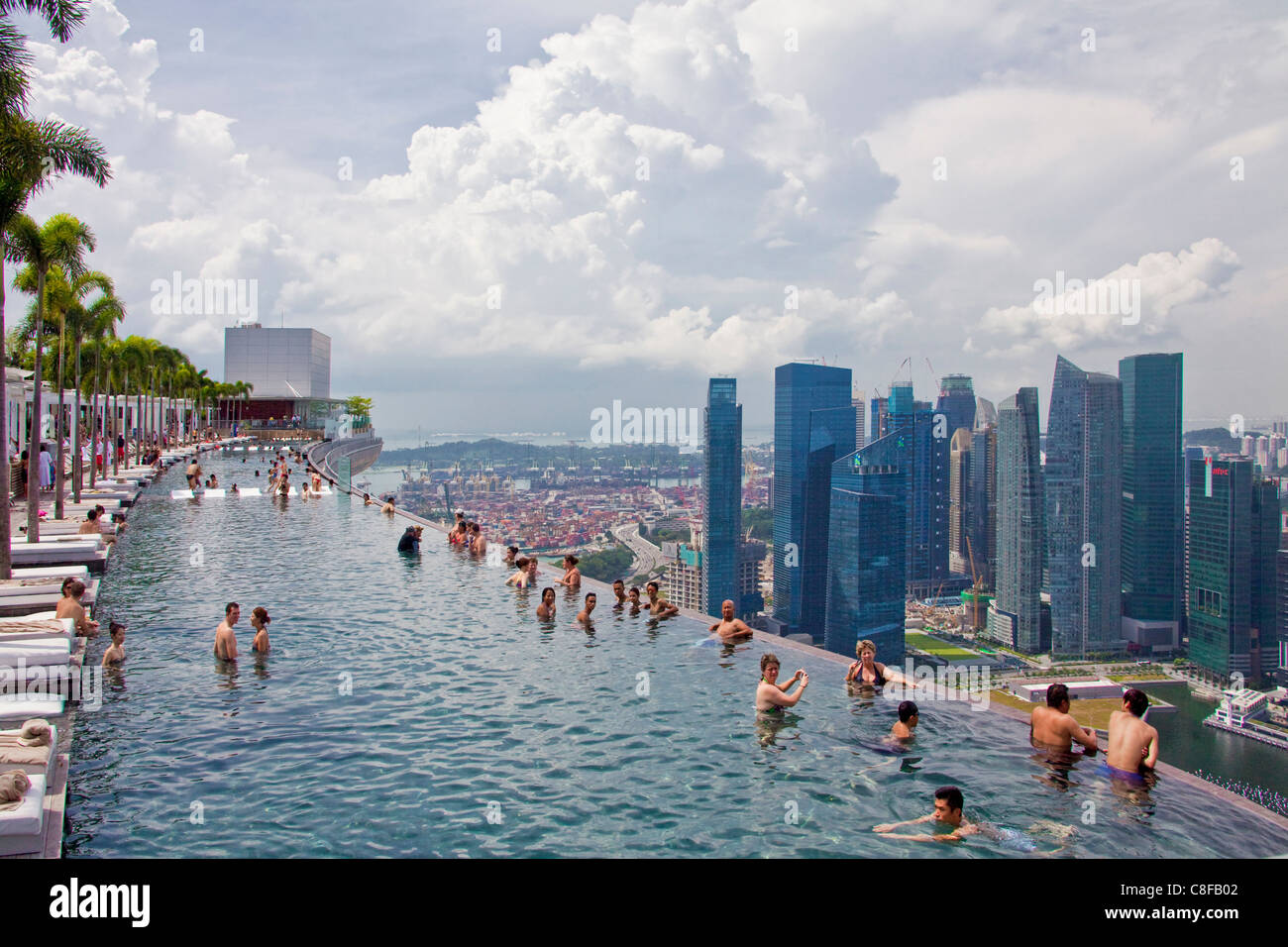 Singapore asia marina bay hotel hotel pool look glance at stock photo royalty free image for Hotel with swimming pool on roof singapore
