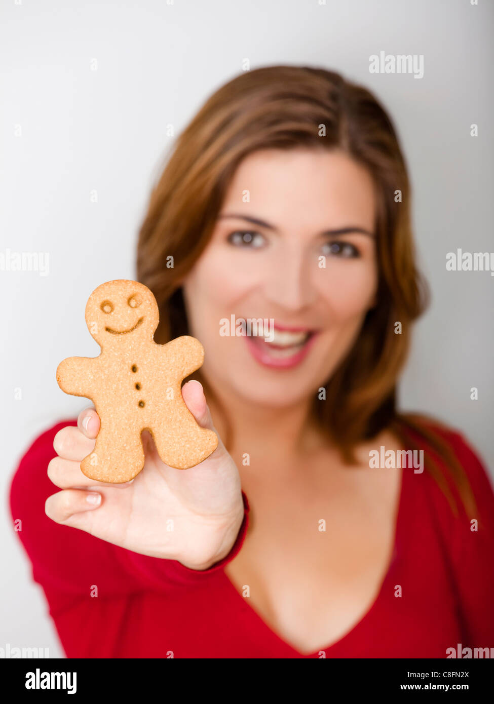 beautiful young woman holding a gingerbread cookie focus is on the stock photo royalty free. Black Bedroom Furniture Sets. Home Design Ideas