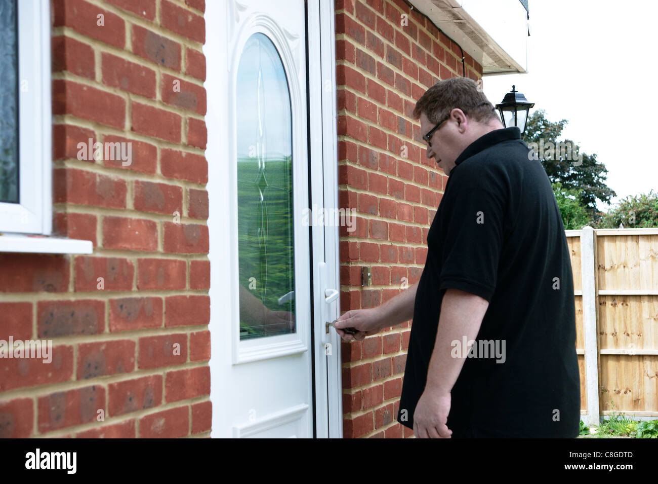 person locking door. Man Locking / Unlocking Front Door Of Property Person