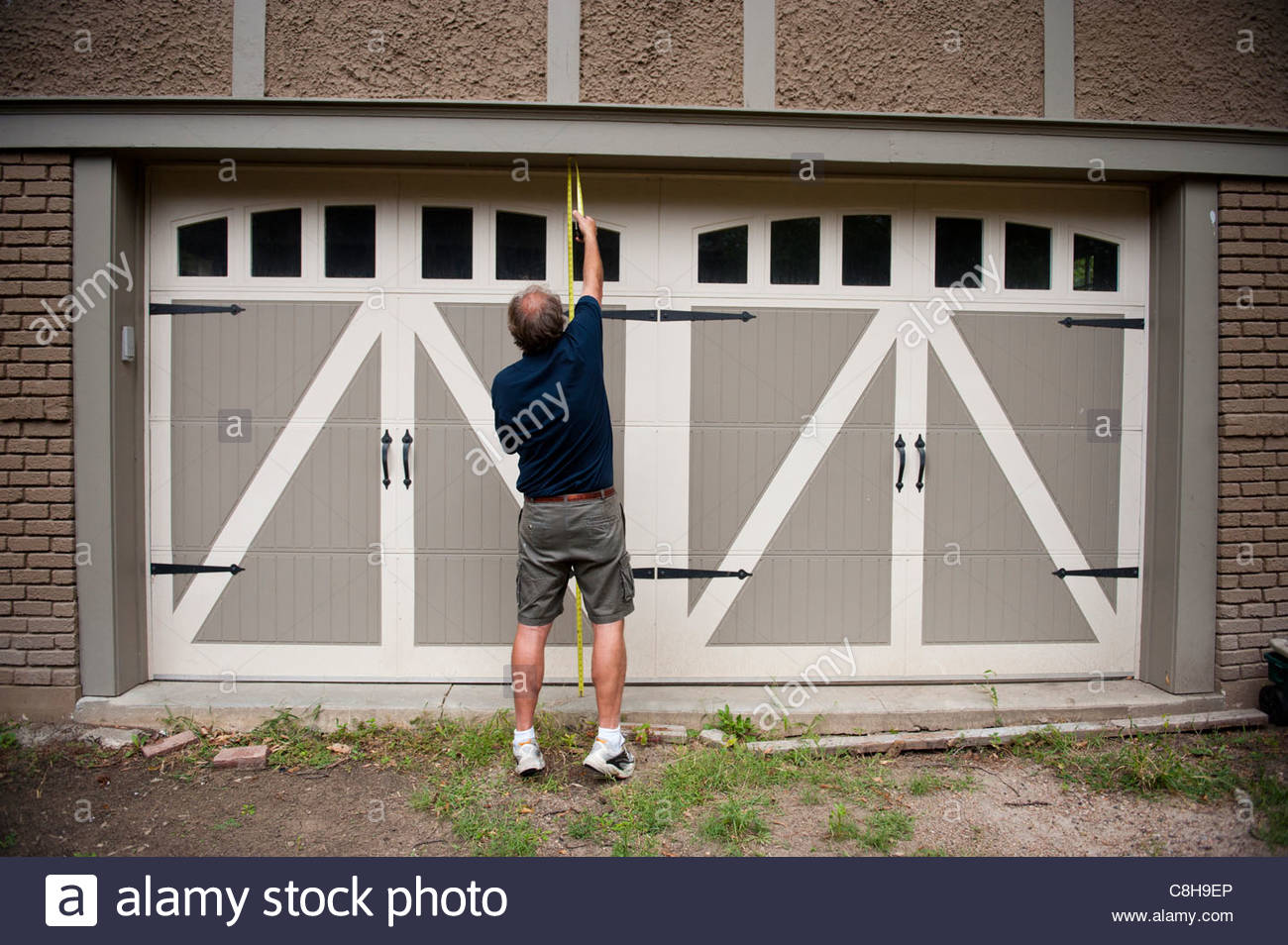 A Man Measures The Height Of His Garage Doors In Lincoln, NE