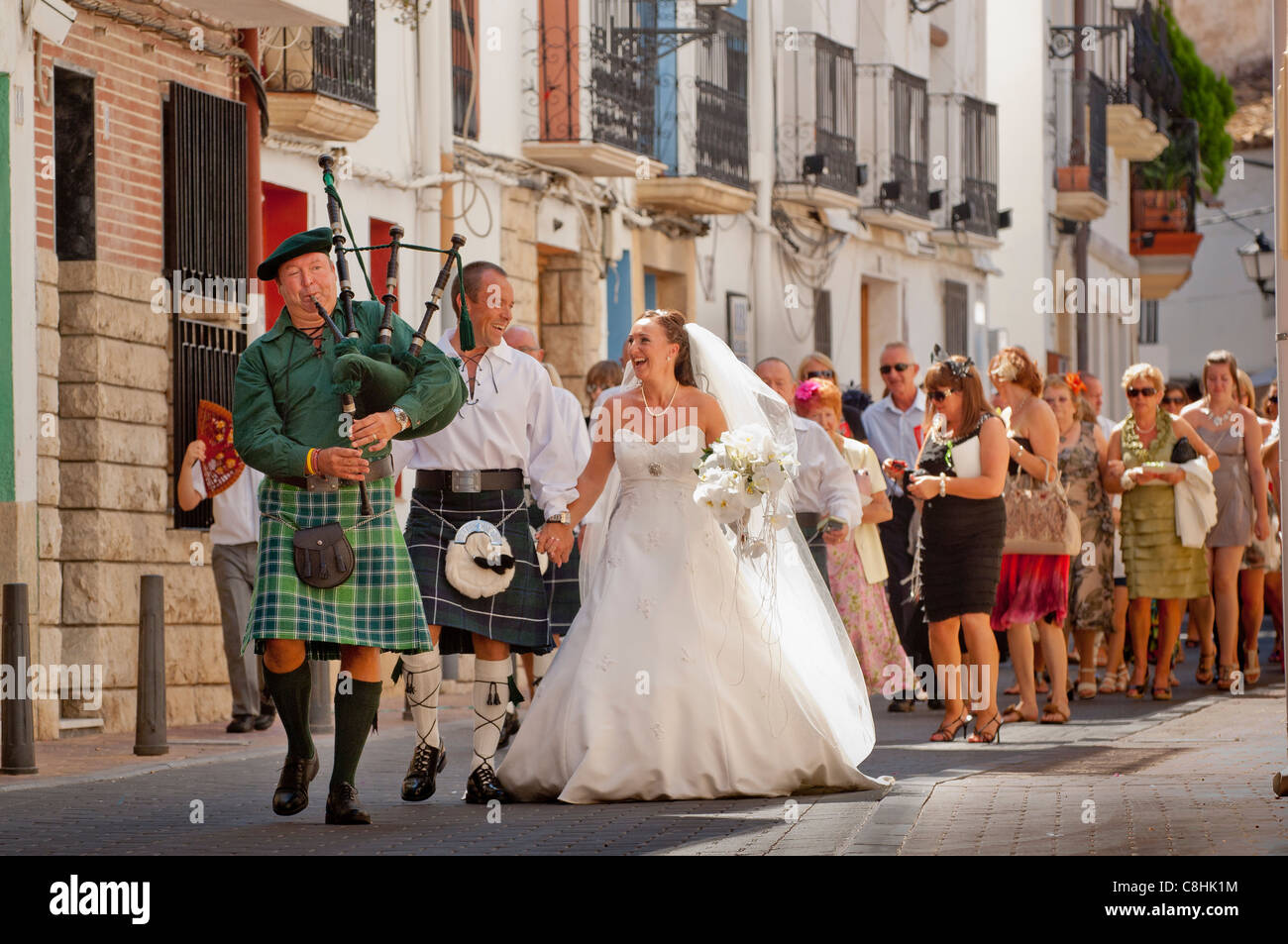 A scots wedding procession goes through the narrow streets of the a scots wedding procession goes through the narrow streets of the spnish village of la nucia in spain picture by brian hickey junglespirit Images