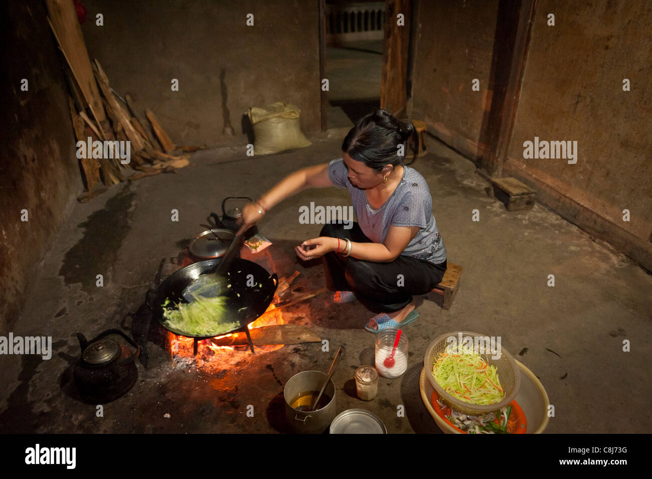 vietnamese woman cooking on an indoor fire pit stock photo  - stock photo  vietnamese woman cooking on an indoor fire pit