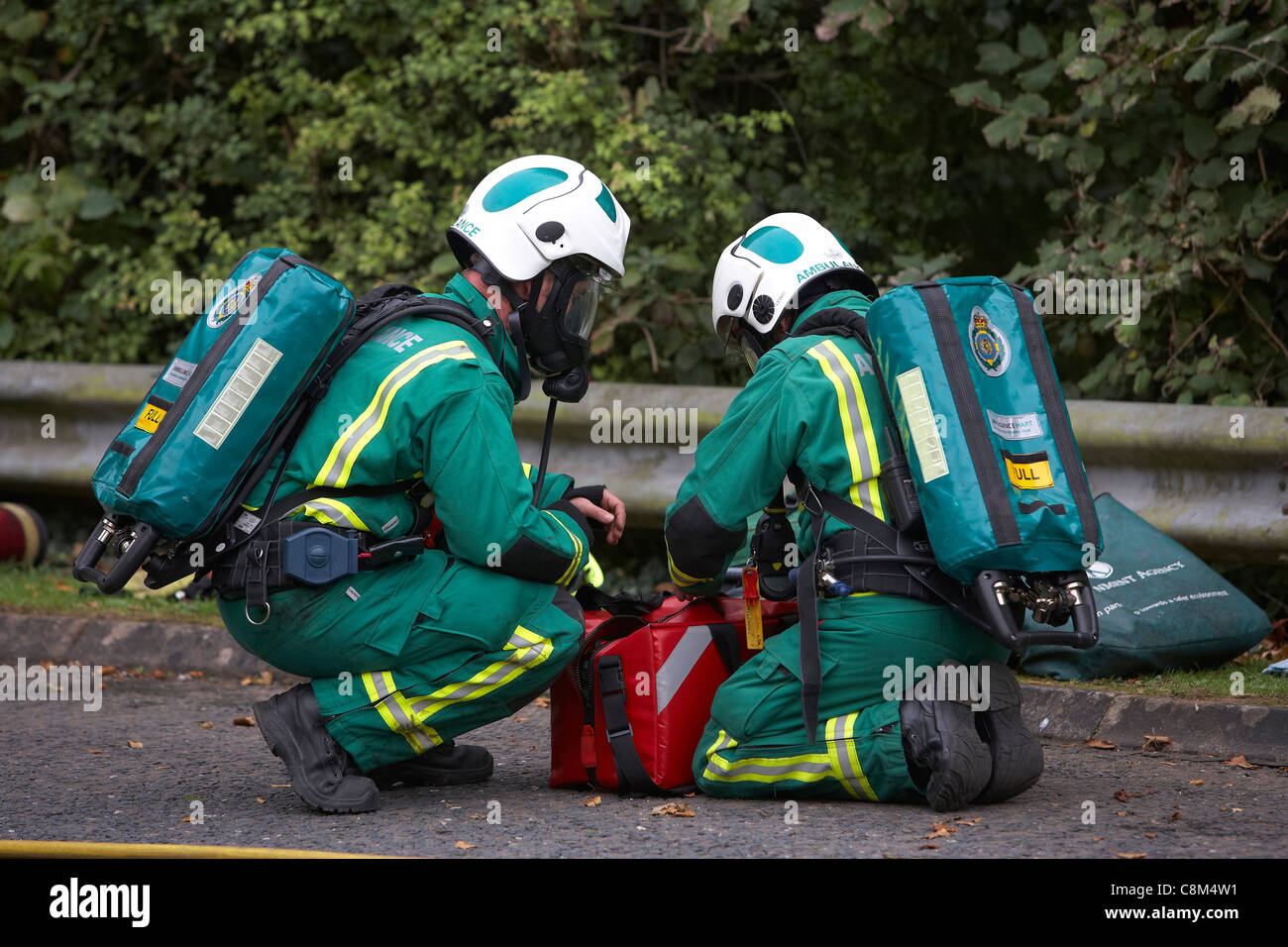 Paramedics wearing oxygen masks attend a road traffic accident Stock ...