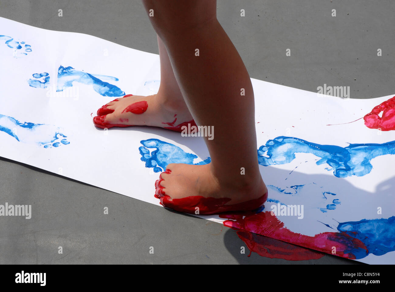 Nursery child painting footprints by walking in paint with ...