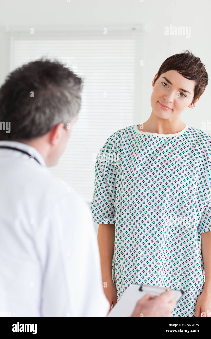 Cute Woman in hospital gown talking to her doctor Stock Photo ...