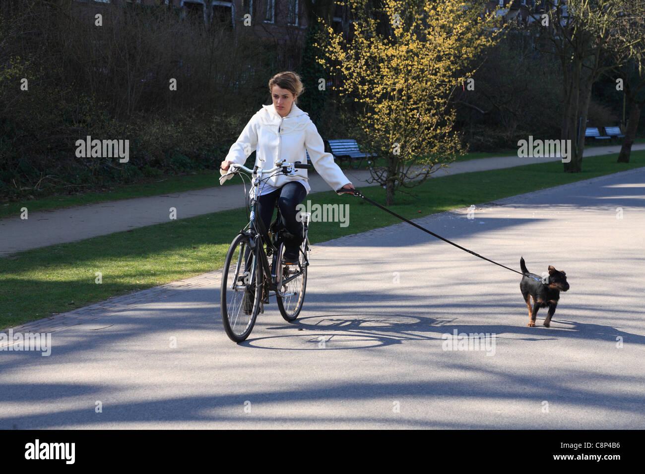 Pretty Girl Riding A Bike Walking Her Dog In The Vondelpark