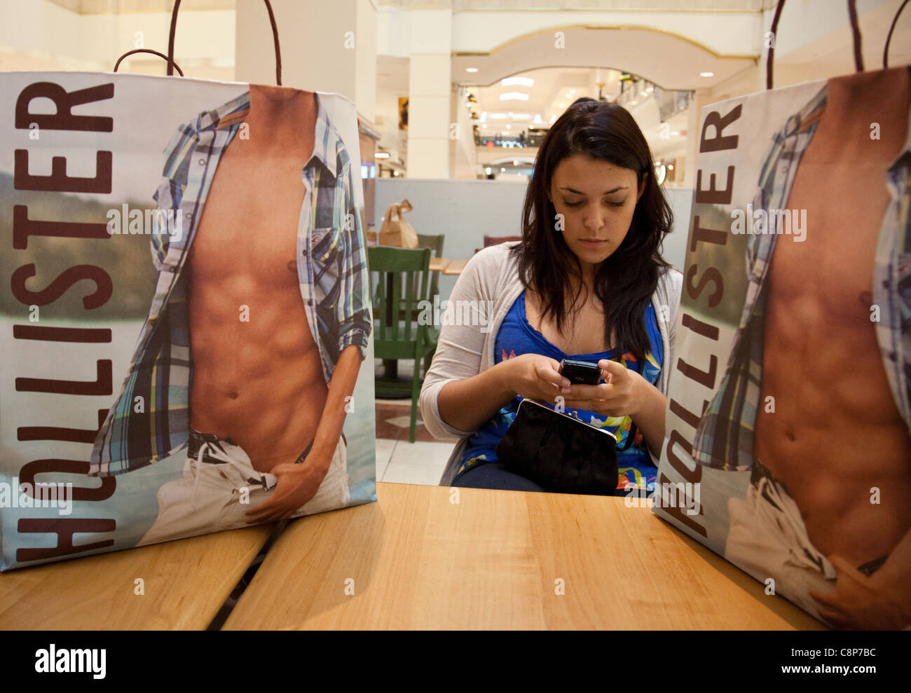 Teenager using cellphone in mall with shopping bags from Hollister ...