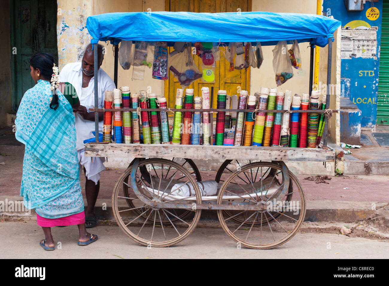 Indian man selling bangles from a wooden cart on an indian street puttaparthi andhra