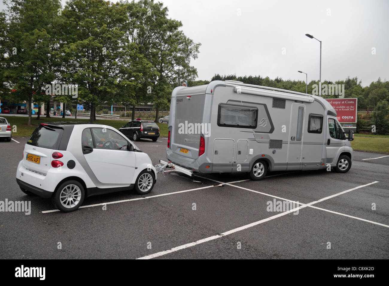 Small Car Camper Small Car Being Towed By A Campervan Parked At The Rownhams