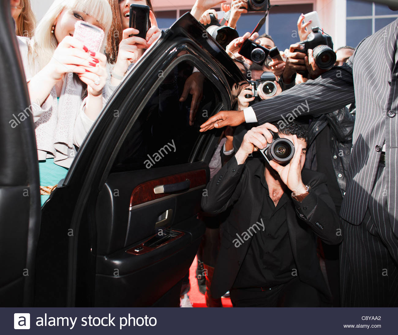 Fans taking pictures with cell phone behind barrier stock photo - Paparazzi And Fans Taking Photos Inside Car Door Stock Image