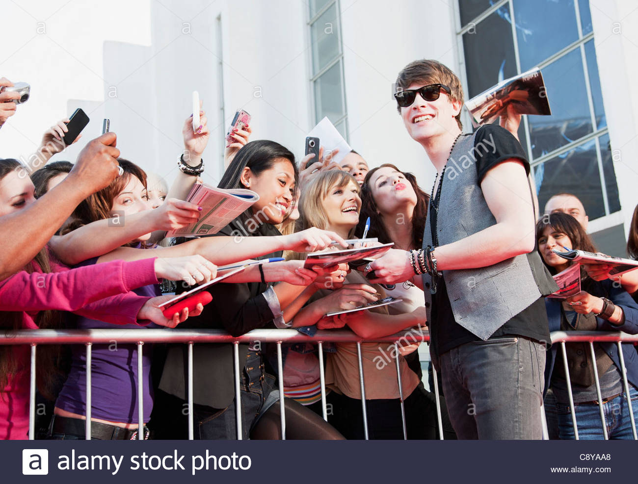 Fans taking pictures with cell phone behind barrier stock photo - Celebrity Signing Autographs For Fans