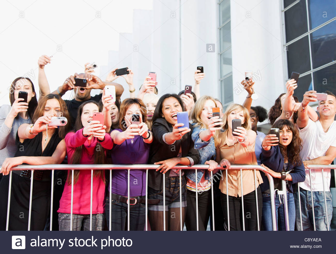 Fans taking pictures with cell phone behind barrier stock photo - Fans Taking Pictures With Cell Phones Behind Barrier