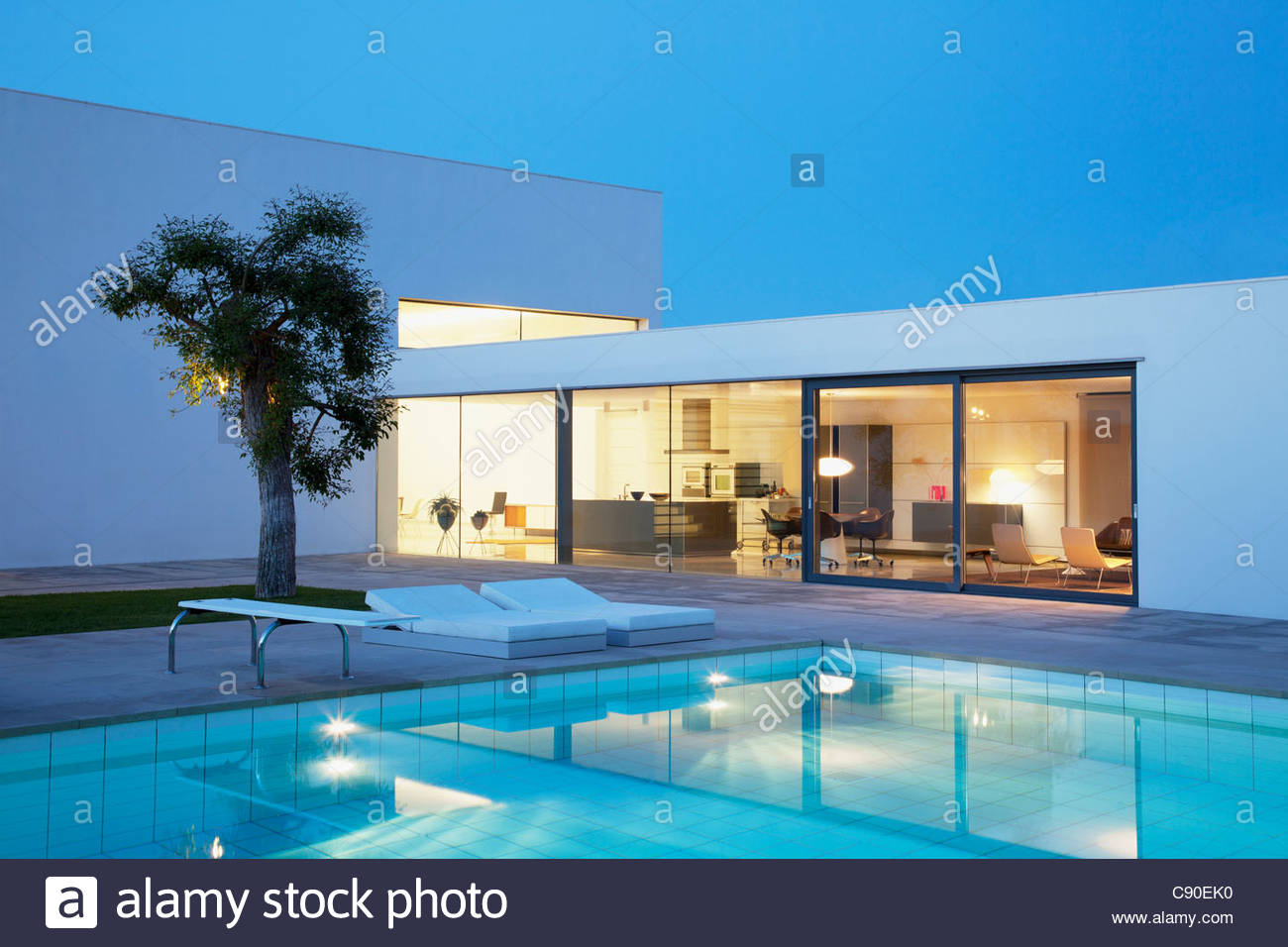 Pool outside modern house at night stock photo royalty for Modern house at night