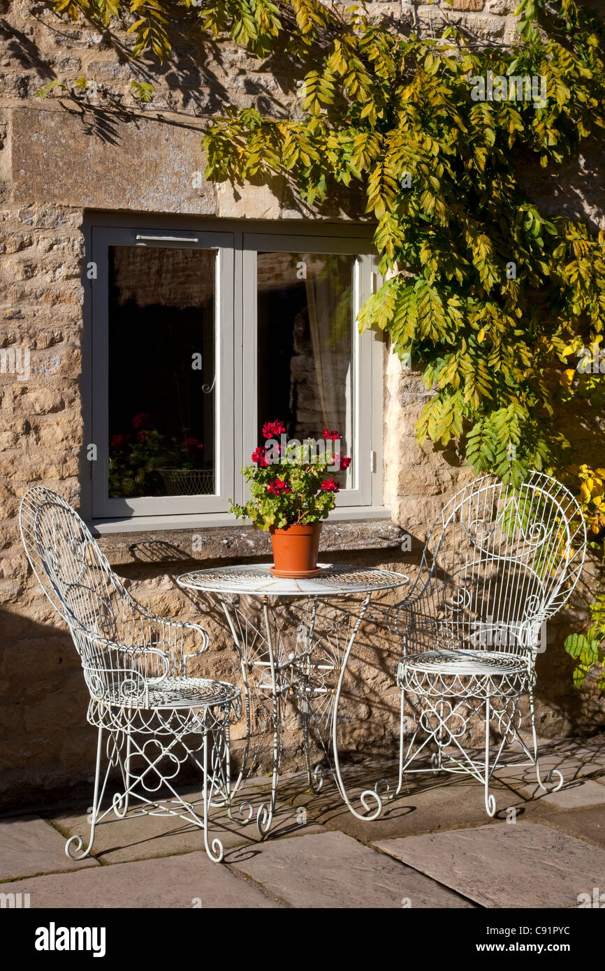 Metal French Styled Outdoor Chairs And Table With Pot Plant Outside House  On Stone Patio Area